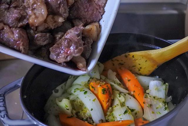 鍋に肉を入れているところ