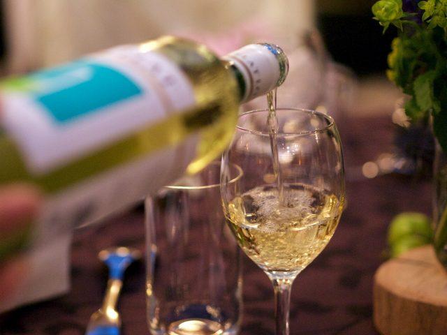 グラスに白ワインを注ぐ様子