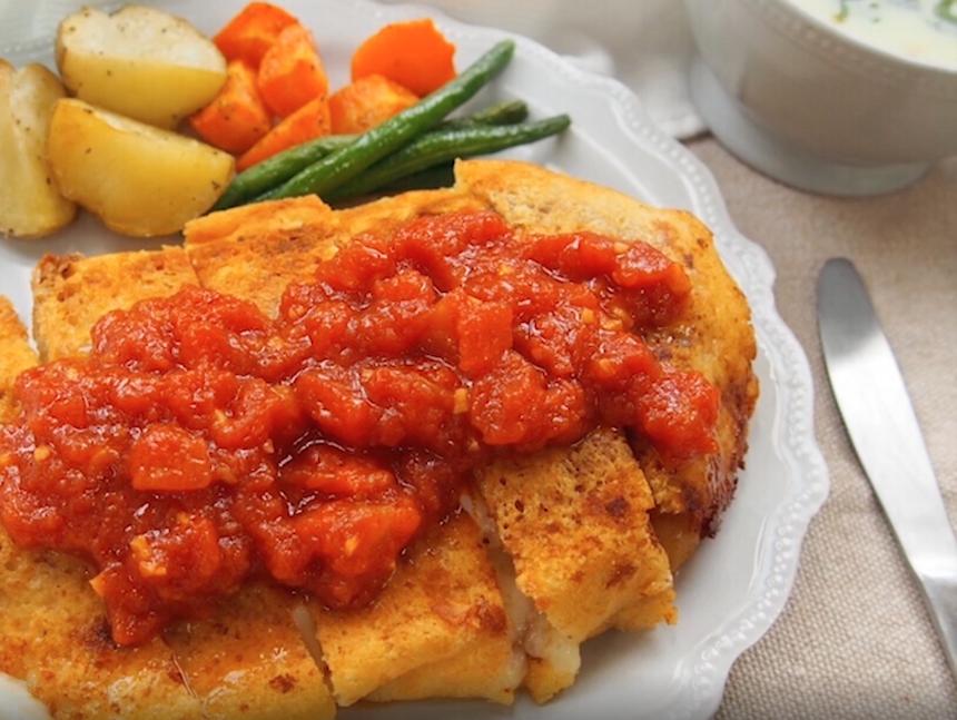 白い丸皿に盛り付けられた鶏胸肉のチーズ焼き