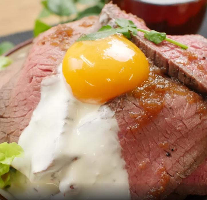 卵黄とソースが垂れそうなローストビーフ丼