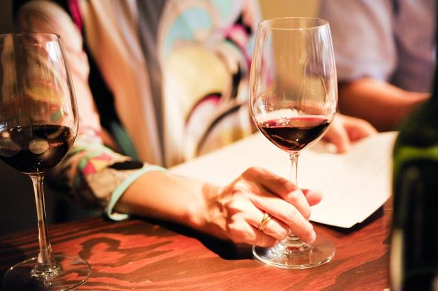 テーブルで赤ワインが入ったグラスをもつ女性