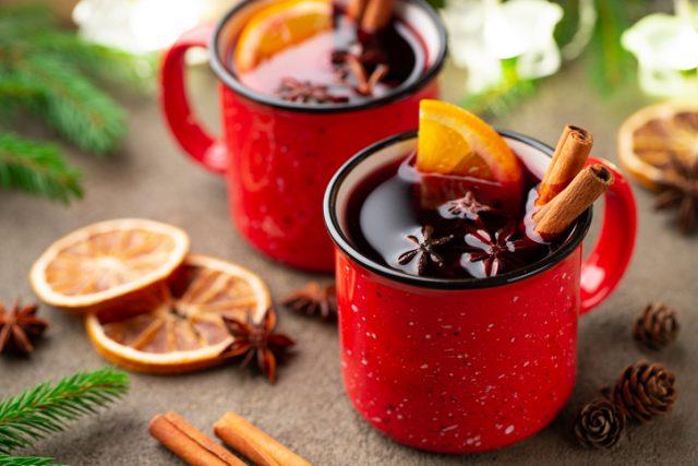 赤いマグカップに入ったスパイスやオレンジ、ホットワイン
