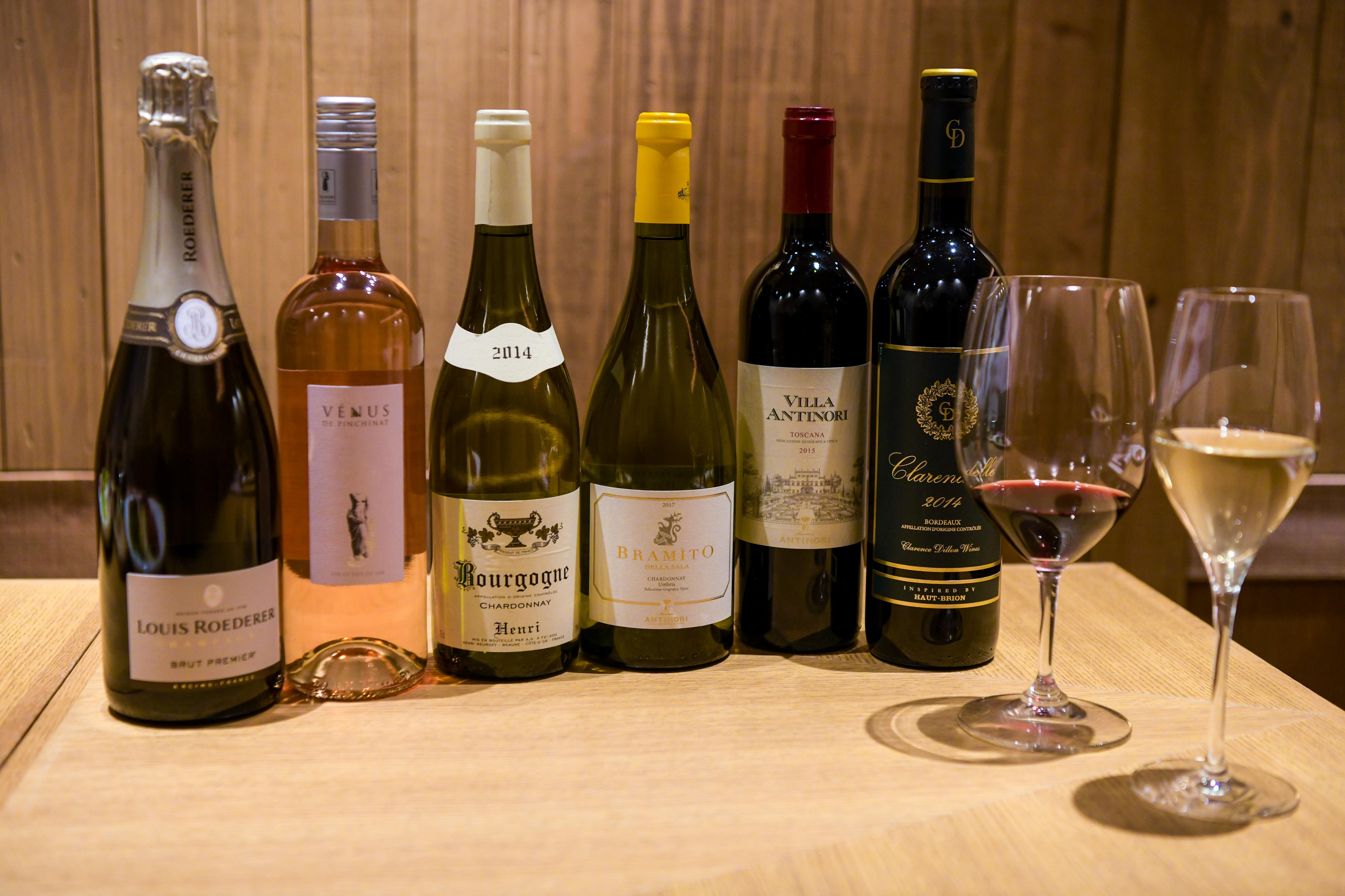 テーブルの上に並ぶ2つのワイングラスと数種のワイン