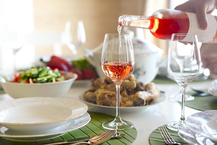 テーブルの上のグラスにロゼワインを注ぐ