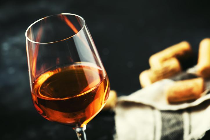 グラスに入ったオレンジワインとコルク