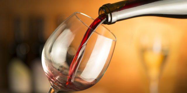 赤ワインをボトルからグラスへ注いでいる