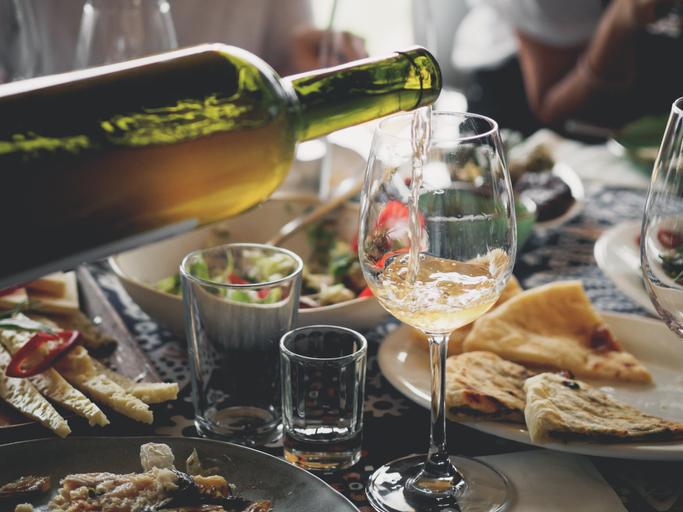 グラスに注がれる白ワインとたくさんの料理