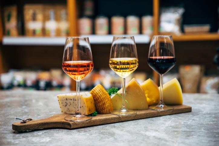 オレンジ、白、赤ワインが注がれた3つのグラスとチーズ