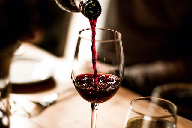 ボトルからワイングラスに赤ワインが注がれている