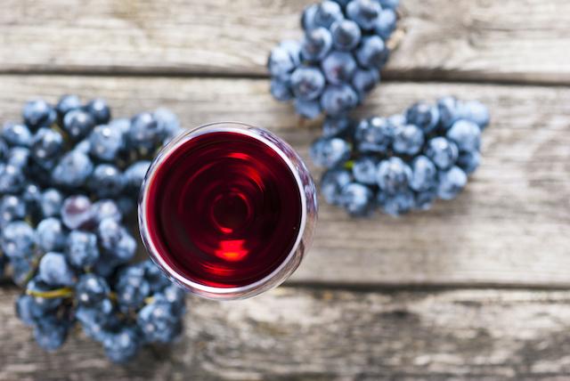 木のテーブルに置かれた黒葡萄と赤ワインが入ったグラス