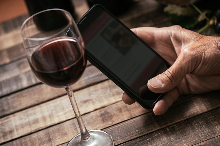 スマートフォンでワインの情報を調べる人