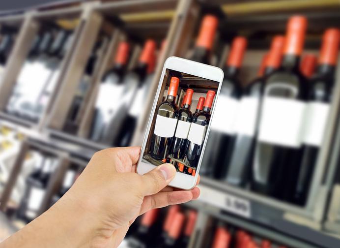 ワインボトルをスマートフォンで撮影する人