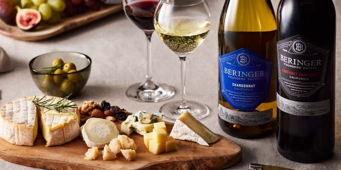グラスに入ったワインとカッティングボードに盛り付けたリーズやフルーツ
