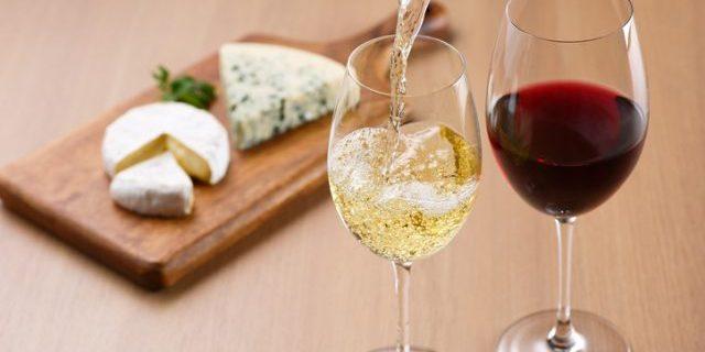チーズが並ぶテーブルで白ワインがグラスに注がれている