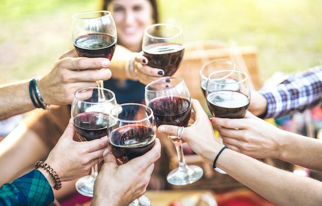グラスの赤ワインを片手にグラスを合わせている様子
