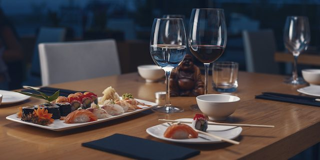 テーブルに並んだ寿司やグラスワイン