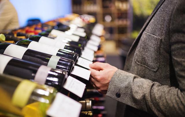 ワインショップでワインを選んでいる男性