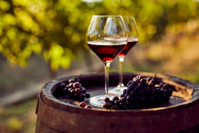 樽の上にワイングラスとブドウが置かれている様子