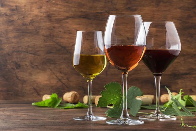 白ワイン、ロゼワイン、赤ワイン入りのワイングラスが並んでいる様子
