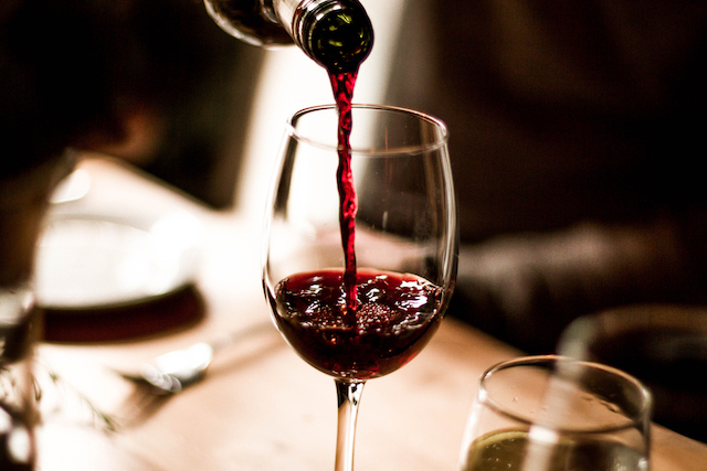 お皿を敷いたグラスに赤ワインに注いでいる