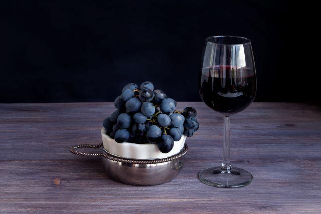 テーブルに置かれた赤ワインのグラスと、器に盛られたブドウ