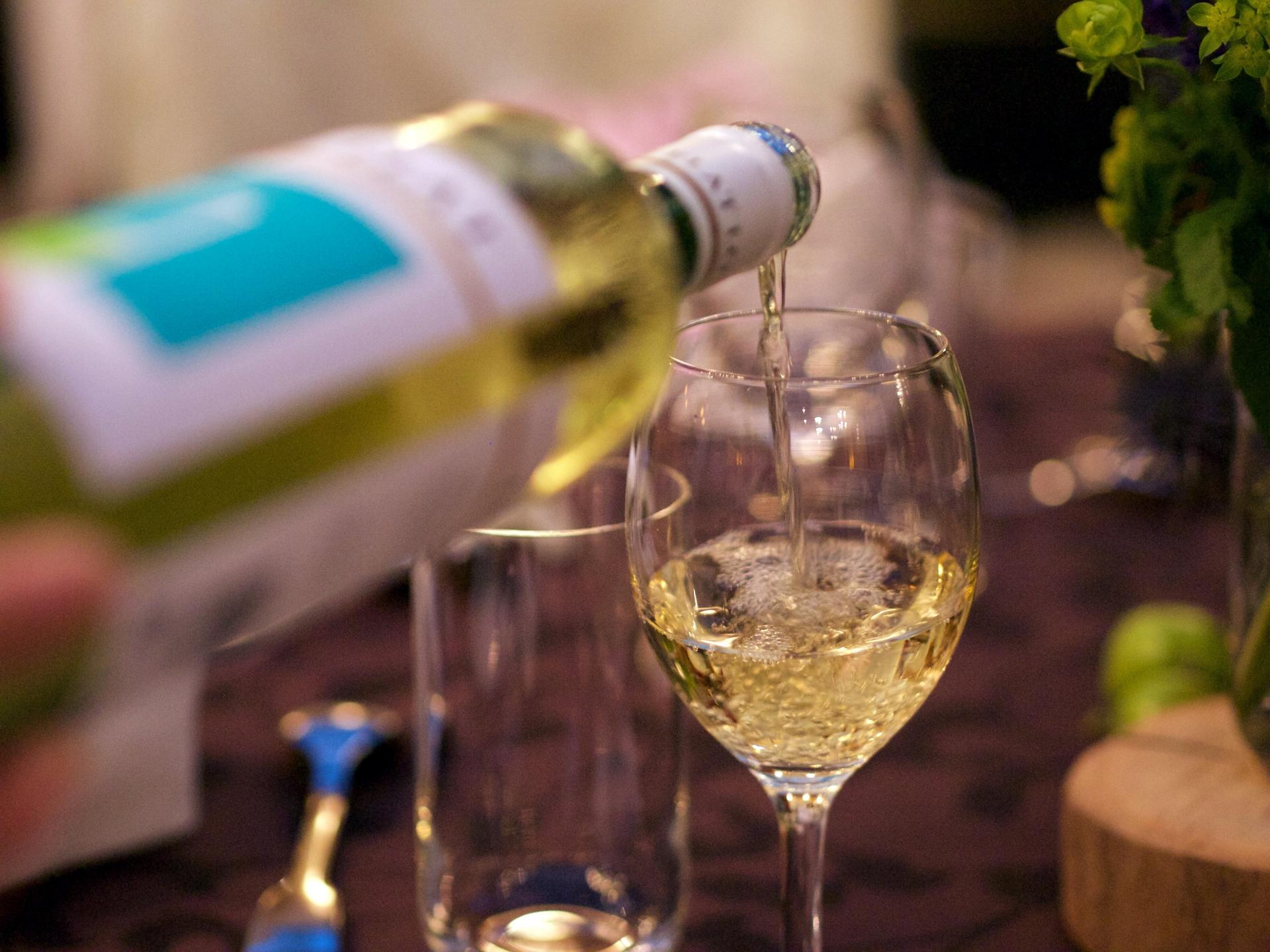 グラスに白ワインを注いでいる様子