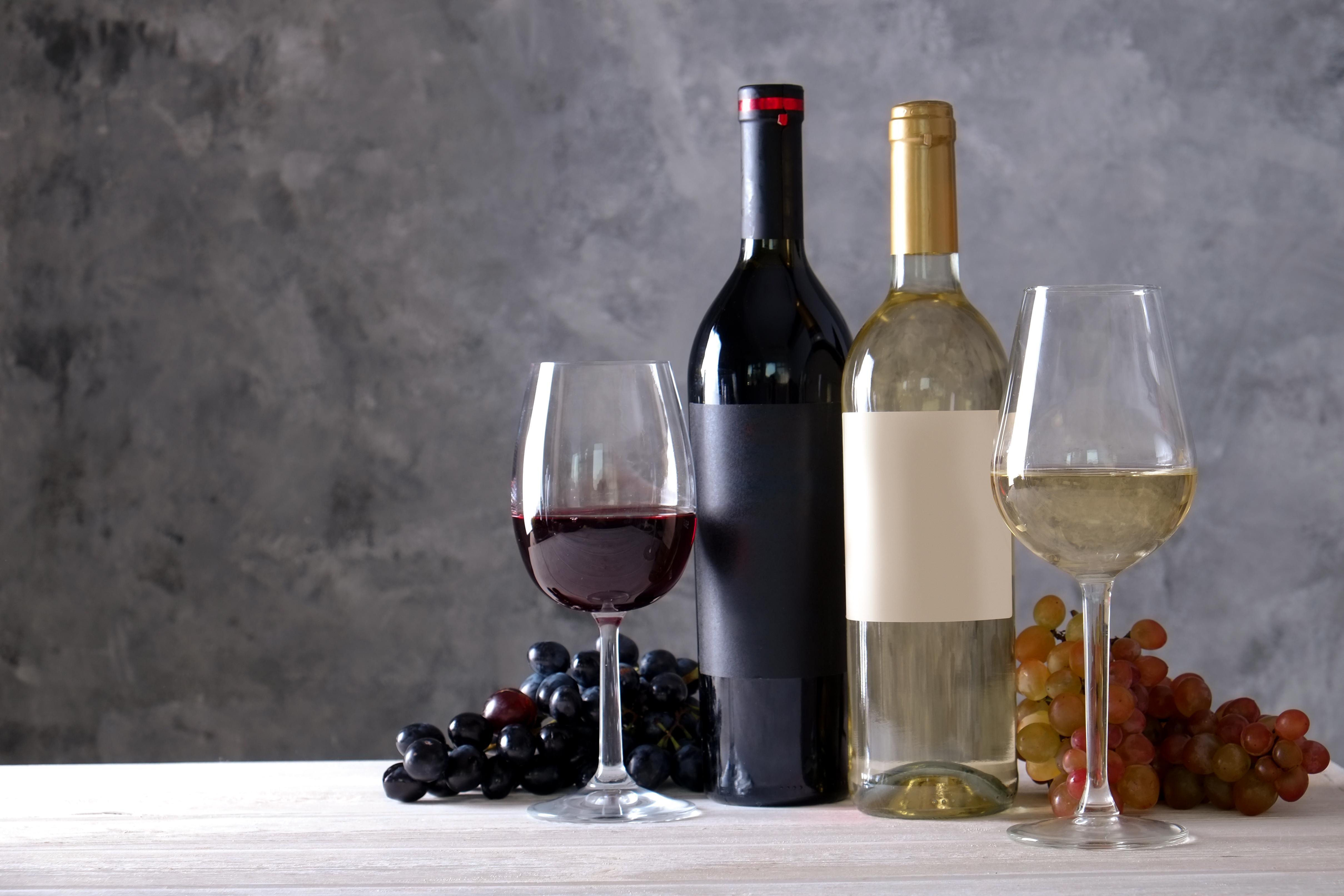 テーブルの上に置かれた赤ワインと白ワインのボトルとグラス、2種のブドウ