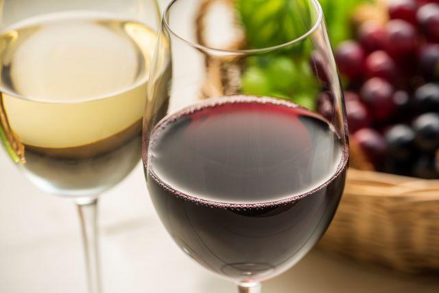 テーブルに置かれた赤・白のワイングラスとブドウ