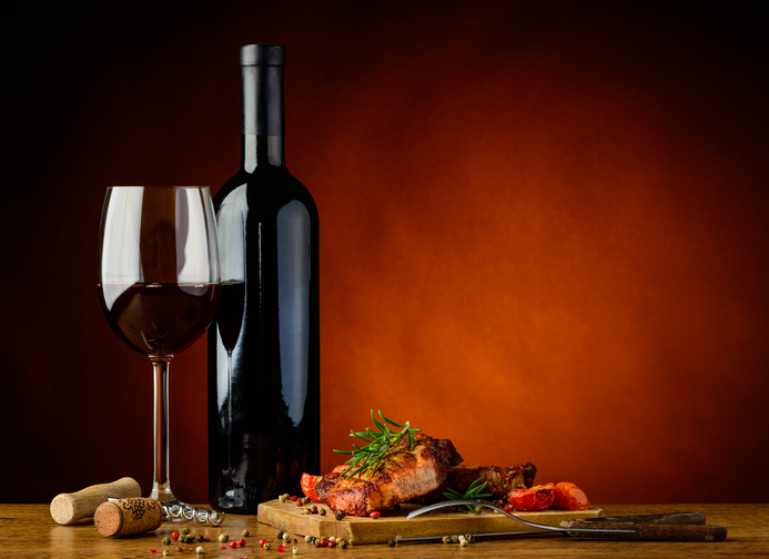 肉料理のプレートとワイン入りのグラス&ボトル