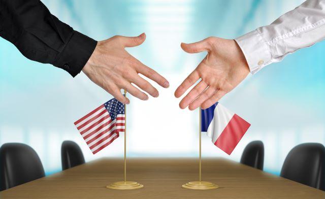 アメリカ・フランス国旗の前で握手しようとしている様子
