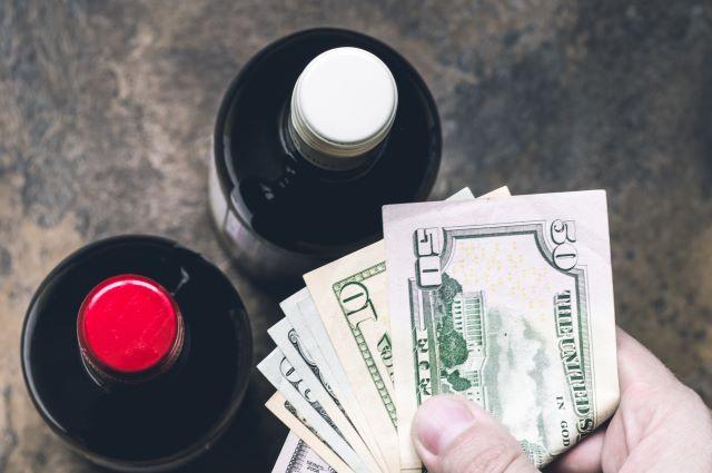 ワインボトルの上で紙幣を出している様子