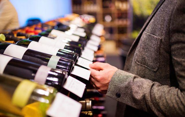 男性が棚に並ぶワインを選んでいる様子