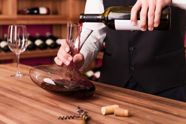 男性ソムリエが、デキャンタに赤ワインを注いでいる様子