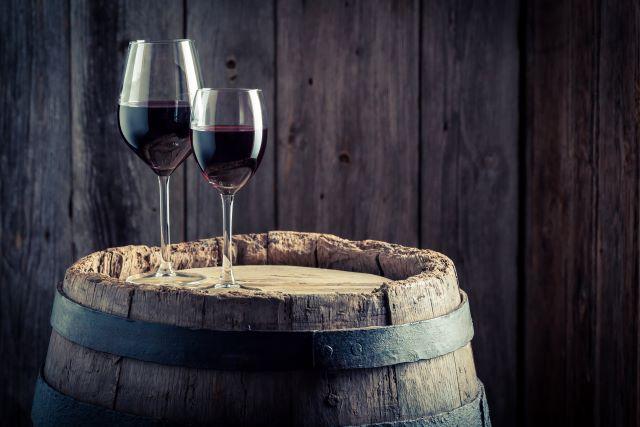 古樽の上に置かれた、2つの赤ワインのグラス
