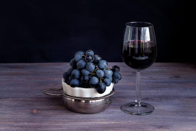 黒ぶどうが入った小さなかごと赤ワインが入ったグラス
