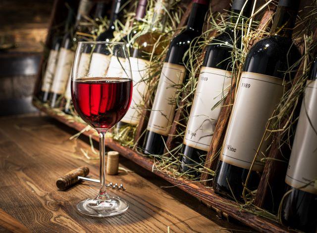 木箱に入れられたワインボトルの前に置かれた、赤ワイングラス