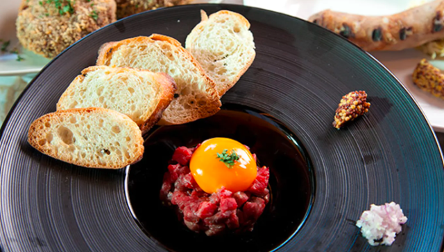 黒皿に盛られた牛肉のタルタルとスライスしたパン
