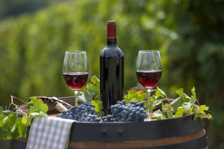 ブトウ畑の樽に置かれた赤ワインボトルとグラス