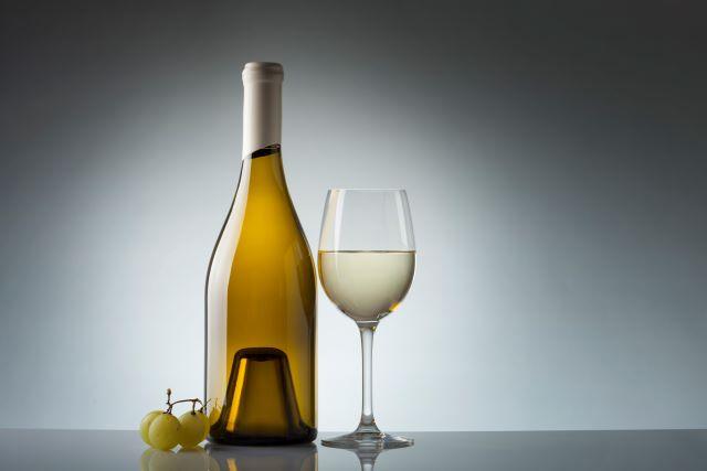 台に置かれた白ワインのボトルとグラス、ブドウの実