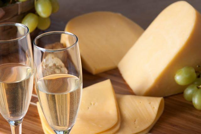 テーブルに置かれたシャンパングラス、チーズ、白ブドウ