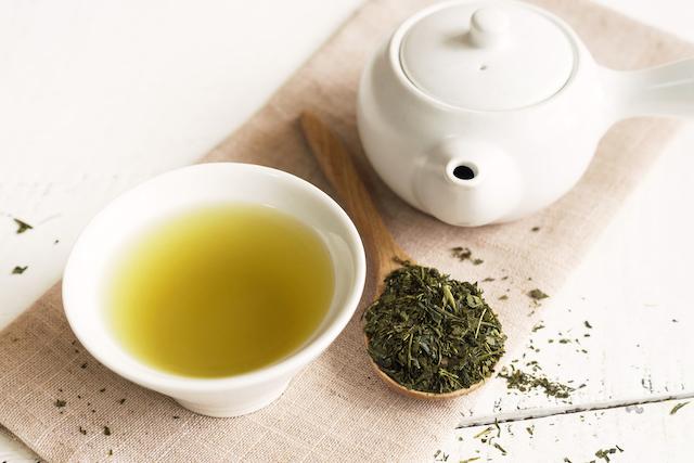 白い急須と湯呑みに入った緑茶と木のスプーンに盛られた茶葉