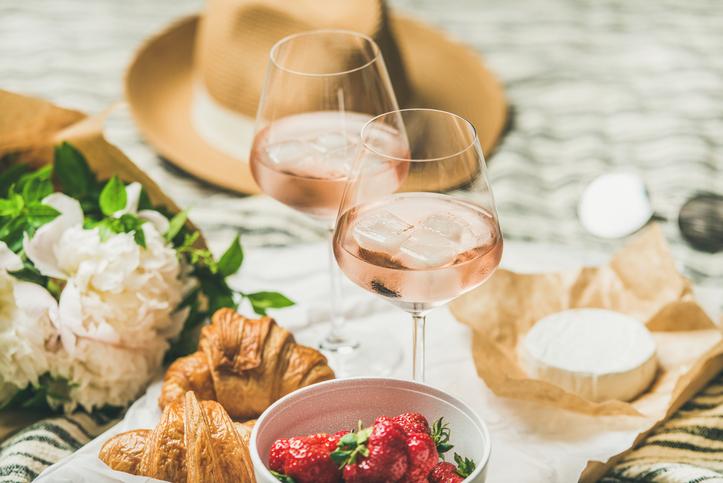 ロゼワインとクロワッサン、イチゴなどがレジャーシートに並ぶ