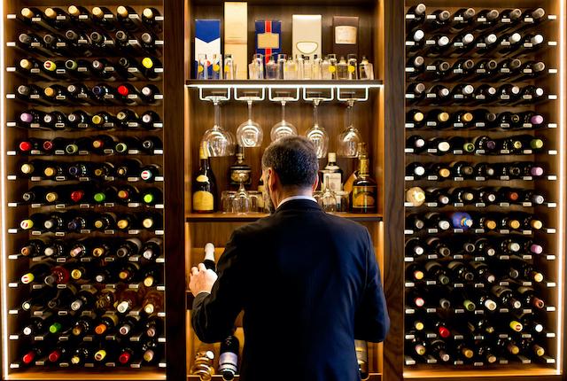 ワインセラーの前でワインを選んでいる男性