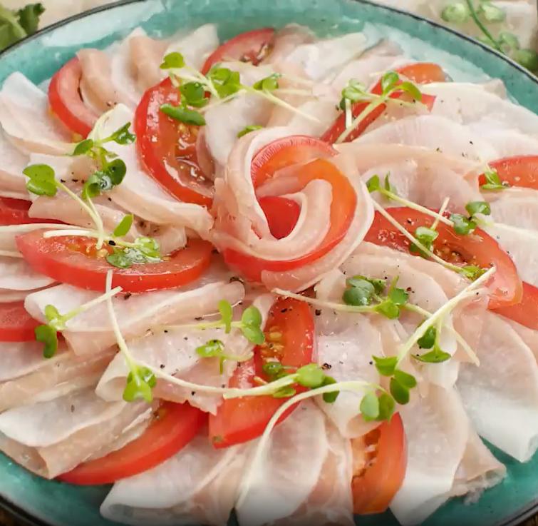 青緑の皿に盛られた、生ハム大根のカルパッチョ風サラダ