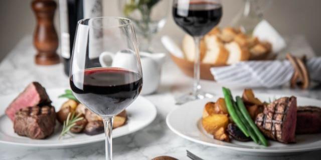 アイキャッチ_テーブルの上に並ぶ赤ワインと料理