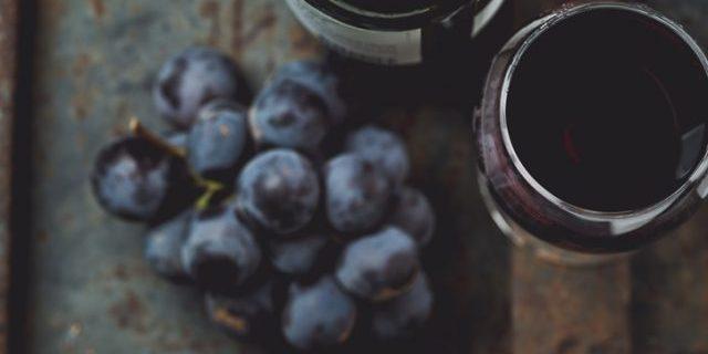 ブドウと赤ワインが机に並ぶ