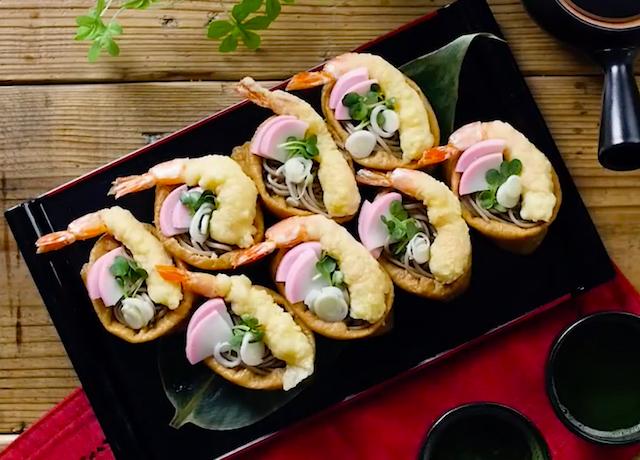 黒いお皿に盛られた海老の天ぷらがのったそばいなり