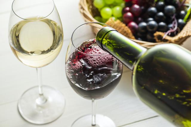 注がれた白ワインと、赤ワインをグラスに注いでいる
