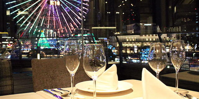 みなとみらいの夜景とテーブルに並べられているグラスとお皿